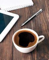 kopje koffie, tablet en notebook foto