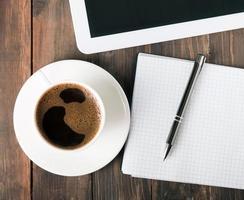 tablet, papieren notitieblok en koffie op de tafel foto