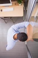 doordachte jonge zakenman permanent tegen glazen wand op kantoor foto