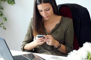 zakenvrouw werken met mobiele telefoon in haar kantoor. foto