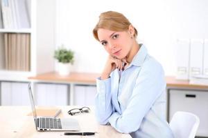 jonge blonde zakenvrouw met laptop op kantoor foto