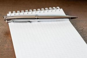 pen en het notitieblok op houten tafel