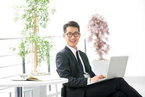 jonge Aziatische zakenman met behulp van tablet, mobiele telefoon op kantoor