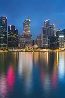 weerspiegeling van kantoorgebouw tijdens schemering in marina bay singapore foto