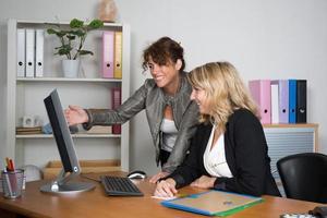 vrolijke zakelijke vrouwen werken op kantoor op een computer foto