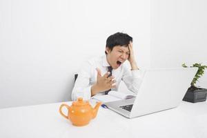medio volwassen zakenman die met laptop op bureau in bureau schreeuwt foto