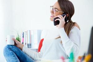 mooie jonge vrouw met behulp van haar mobiele telefoon op kantoor. foto