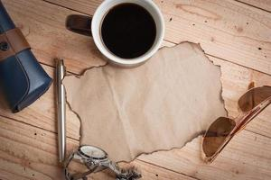 zonnebril, pen, horloge, grunge papier en koffie foto