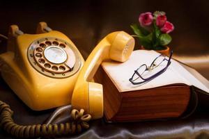 retro telefoon en oud boek. foto