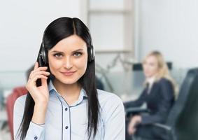 lachende brunette ondersteuning telefoonexploitant met hoofdtelefoon. foto