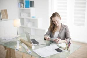 mooie jonge vrouw op de werkplek met behulp van een digitale tablet foto