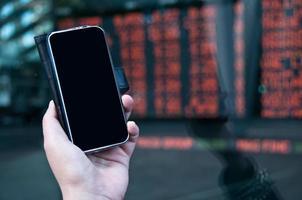 handelsvoorraad op mobiel in de buurt van wisselbord foto