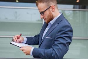 jonge zakenman met baard staande tegenover kantoorgebouw.