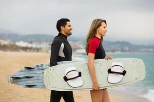 surfers paar op het strand foto