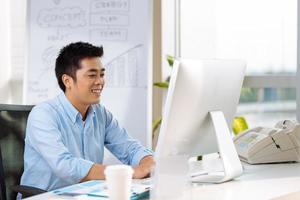 een glimlachende jonge man in een blauw shirt werkt op zijn computer foto