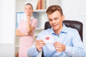 mannelijke executive kijkt opgetogen bij het lezen van de notitie foto
