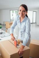 zakenvrouw taping up een kartonnen doos foto