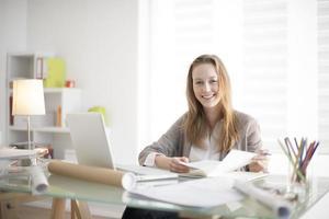 mooie jonge vrouw zit aan haar bureau op de werkplek foto