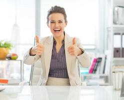 Glimlachende zakenvrouw duimen opdagen foto