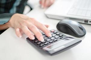 vrouwelijke wijsvinger te typen op een rekenmachine foto