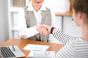 jonge zakenvrouw handen schudden met een klant foto