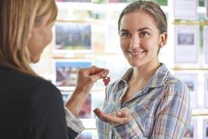 vrouw het verzamelen van sleutels tot onroerend goed van makelaar foto