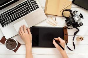 ontwerper gebruikt grafisch tablet in het werk, fotobewerking van bovenaf
