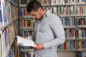 gelukkig mannelijke student met boek in bibliotheek
