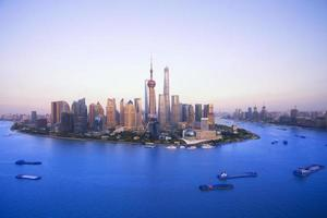 gebouwen langs de huangpu-rivier: west is shanghai bund en oost foto