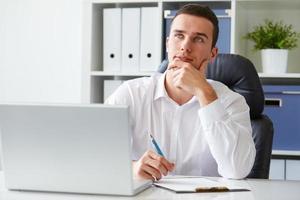 nadenkend jonge zakenman met laptop foto
