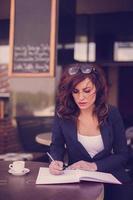 vrouw schrijven in een notitieblok foto