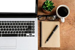 laptop en kopje koffie op oude houten tafel foto