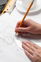 vrouw met een pen over een huis plan te bouwen foto