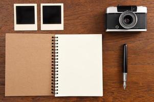 leeg notitieboekje met pen, fotolijsten en camera foto