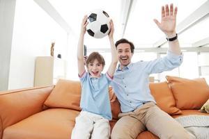 vader en zoon wathcing voetbal foto