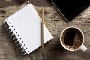 tablet, telefoon, Kladblok en koffie op houten tafel foto