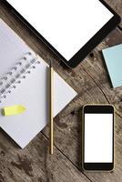 tablet, telefoon en Kladblok op houten tafel foto