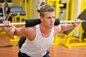 knappe jonge man doet squats in de sportschool foto