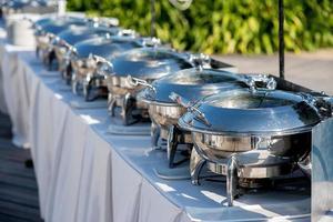buffet tafel met rij van food service stoompannen foto