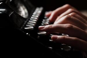 handen schrijven op oude typemachine op houten achtergrond foto