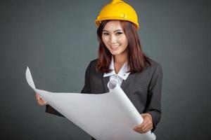 de glimlach van het Aziatische ingenieursmeisje houdt een blauwdruk foto