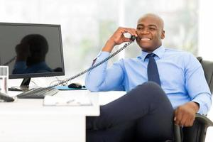 Afro-Amerikaanse zakenman met vaste telefoon foto