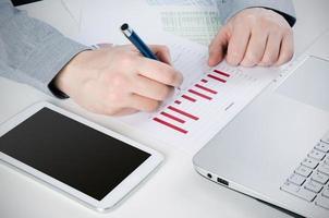 zakenman werken met digitale tablet. rapporteer grafieken op bureau foto