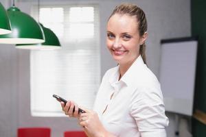 blonde glimlachende onderneemster die smartphone gebruiken foto