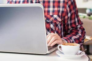 zakenman die bij computerzitting bij koffie in de stad werkt foto