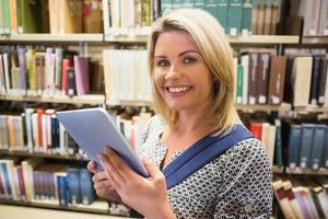 volwassen student met behulp van tablet in bibliotheek