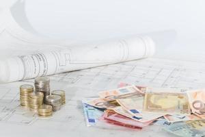 bouwkundige plannen, bankbiljetten en munten foto