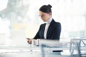 drukke vrouw die op haar laptop werkt foto