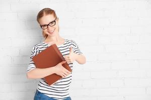 gelukkig succesvolle student meisje met boek duimen opdagen foto