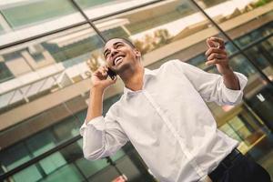 succesvolle knappe op mobiel spreken en zakenman die glimlachen. foto